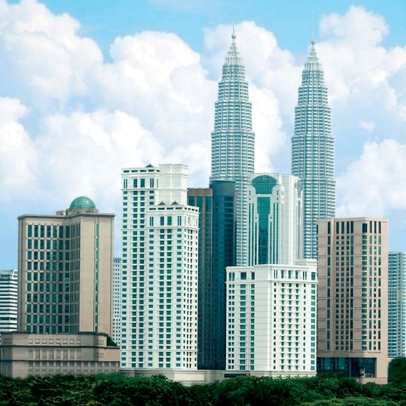 Kuala Lumpur skyline by day showcasing the Petronas Towers and other buildings as well as fluffy clouds and foliage
