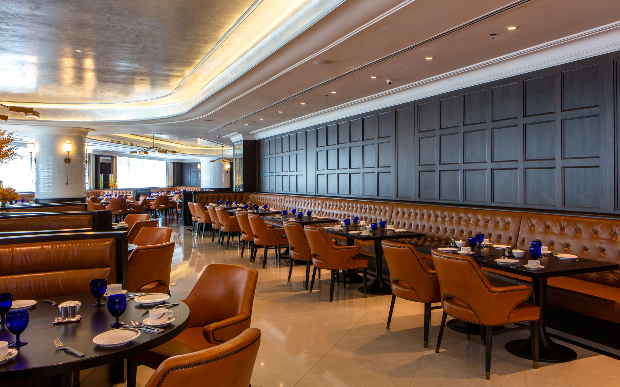 Vast dining room with a dark wood wall lined by banquette seating, plus additional booth seating and natural light