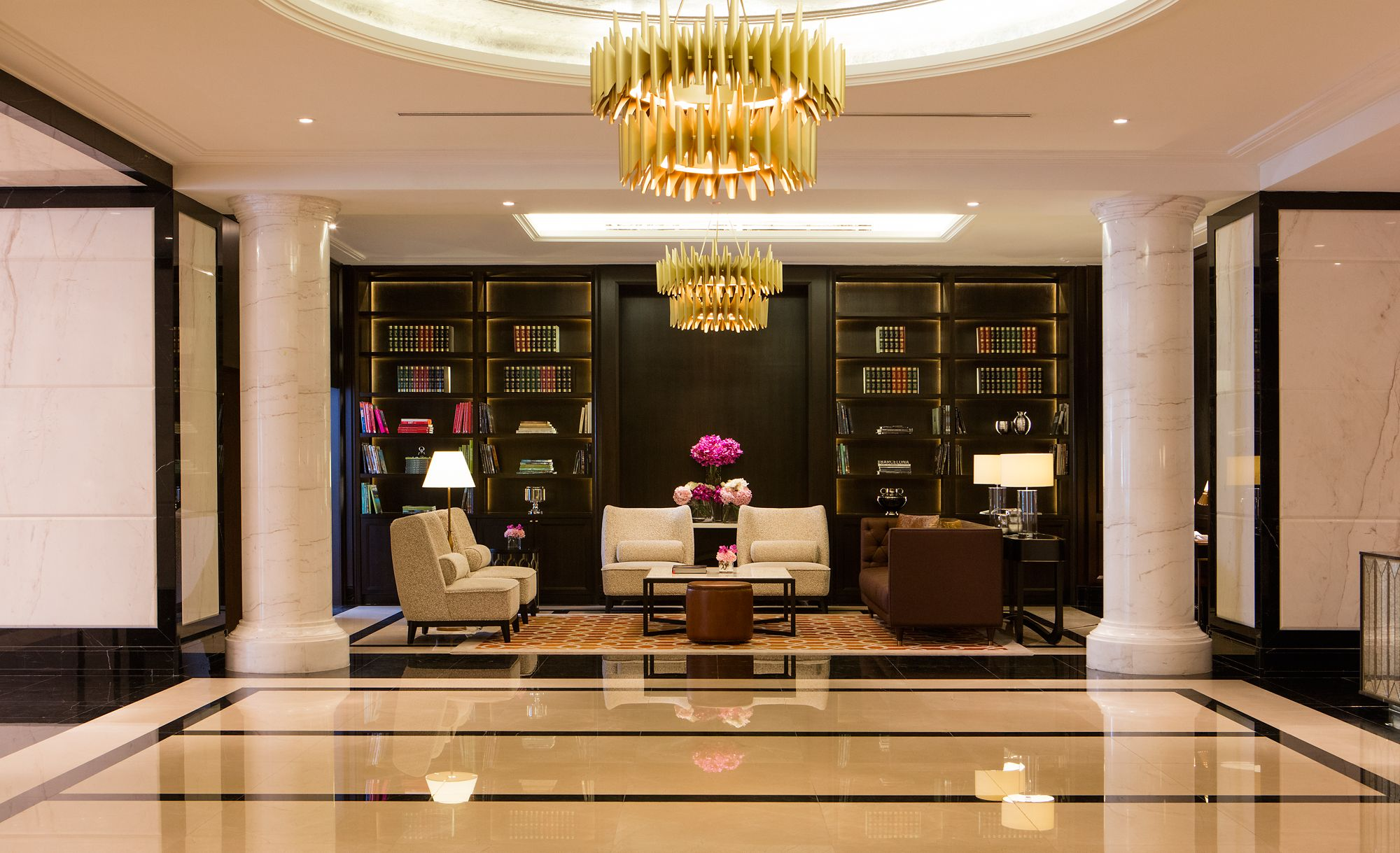 Intimate seating in a space to the side of the lobby where floor-to-ceiling bookcases create a cozy ambience