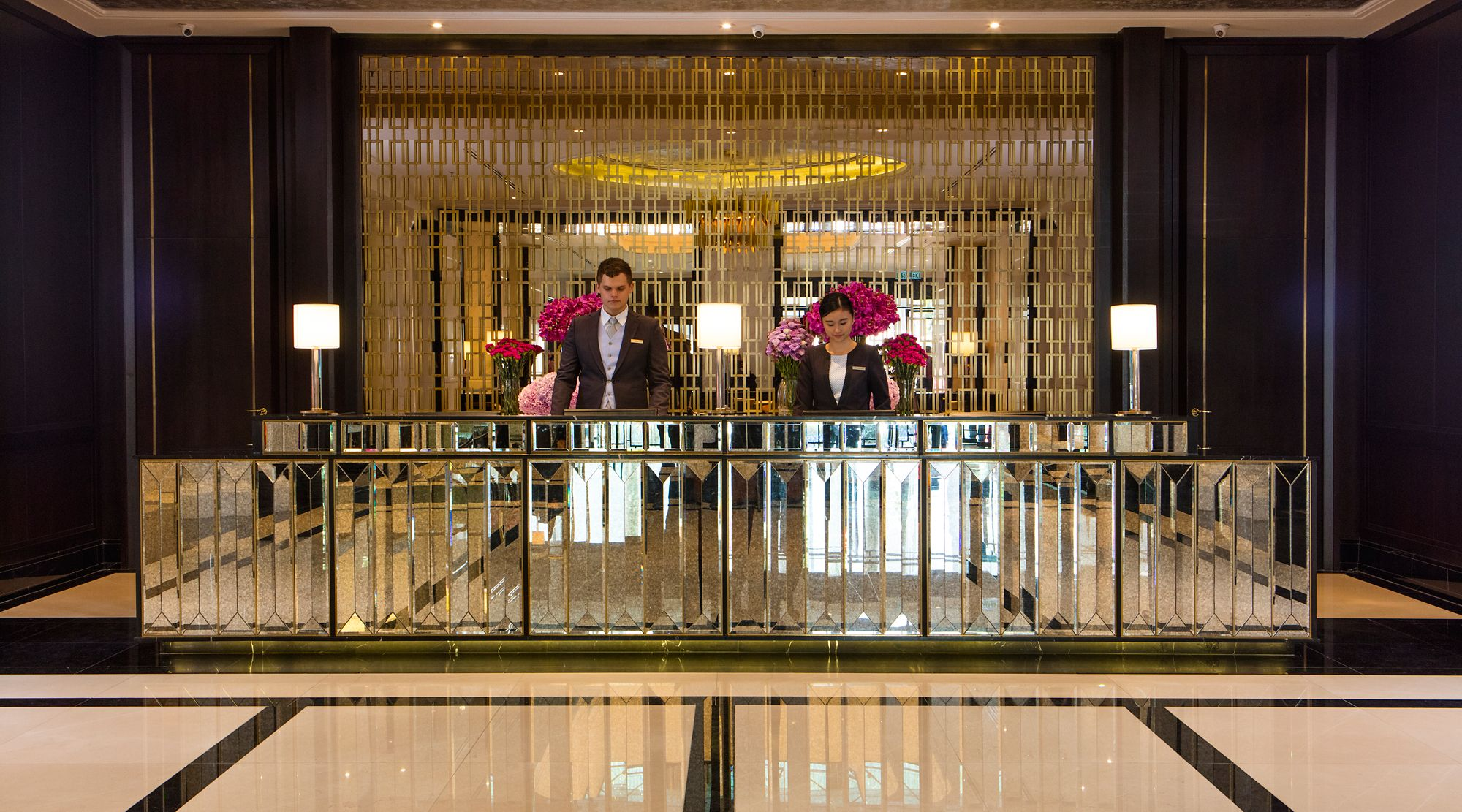 Two associates stand behind the lobby's mirrored check-in desk and in front of another mirror featuring gold patterning