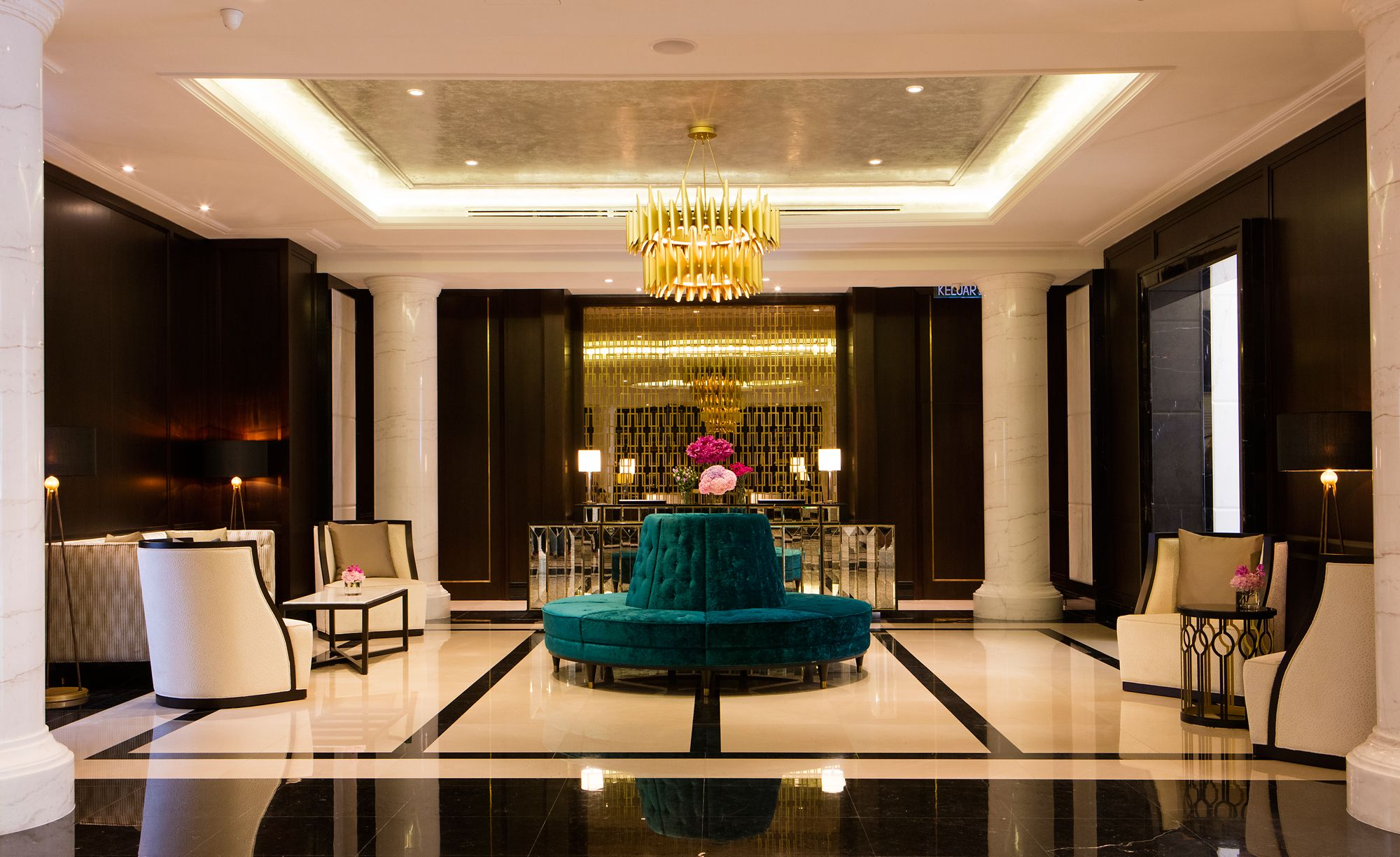 Symmetrical lobby with white marble columns, dark wood wall paneling, a rotund turquoise bench and other seating