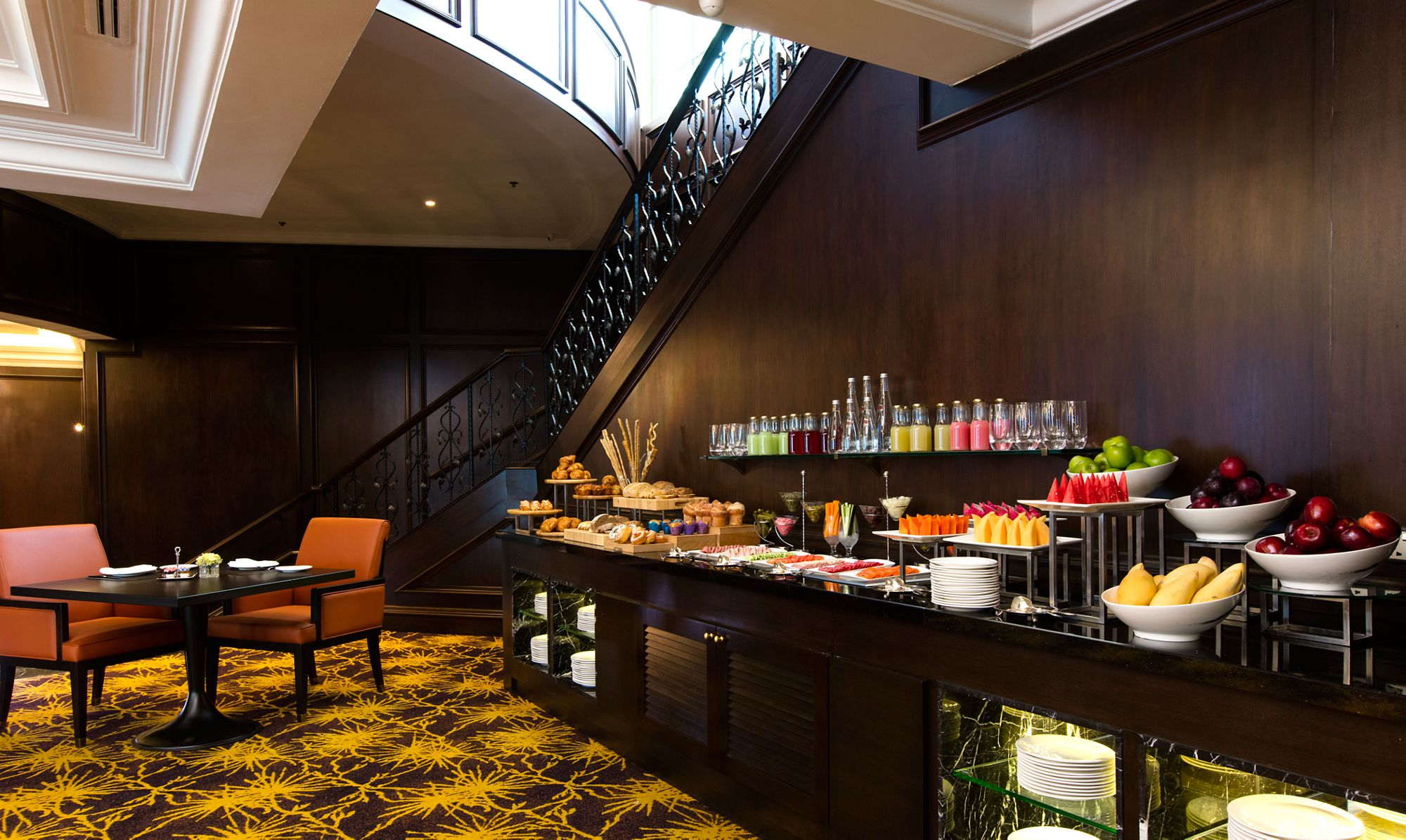 Colorful buffet of fruits, juices and more along a dark wood shelf with seating and a staircase in the background