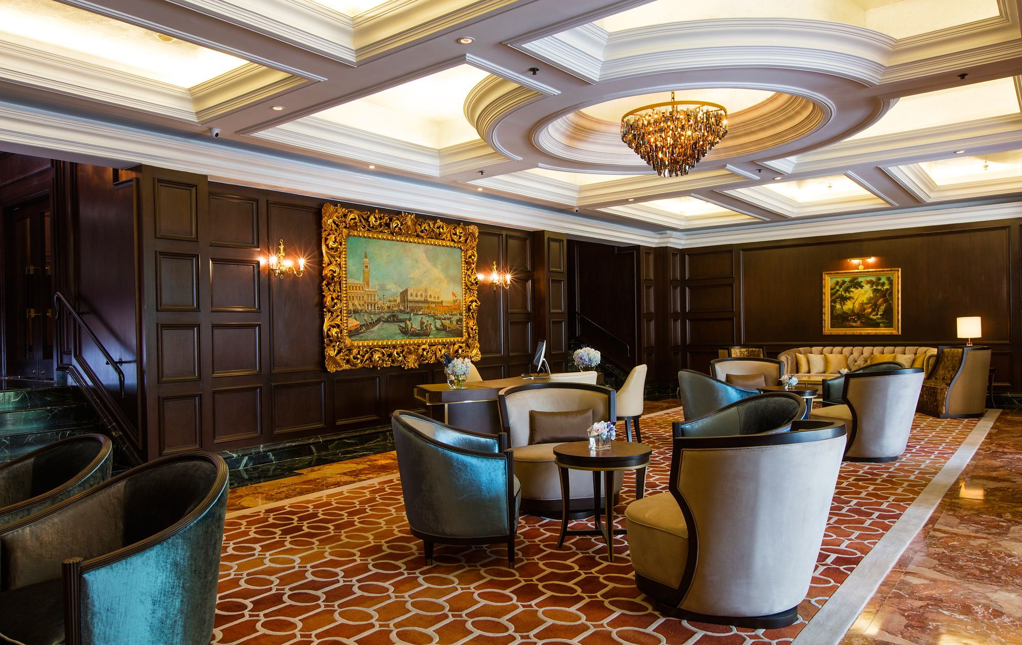 Club Lounge with dark wood-paneled walls, gilt-framed pictures and a white coffered ceiling
