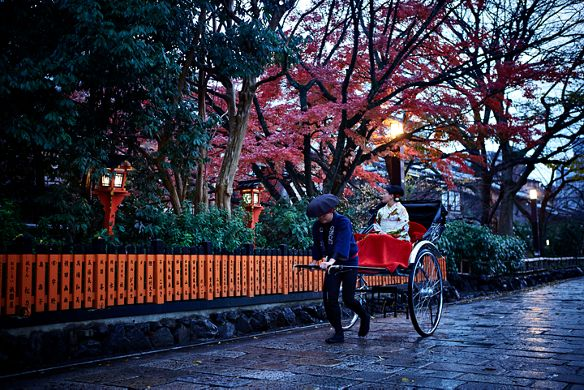 Man pulls a red rickshaw along a leafy street while a woman in a kimono takes in the view