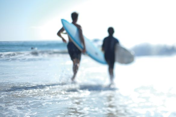 A man and boy with surfboards