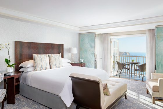 A bedroom leads to a furnished, ocean-view terrace