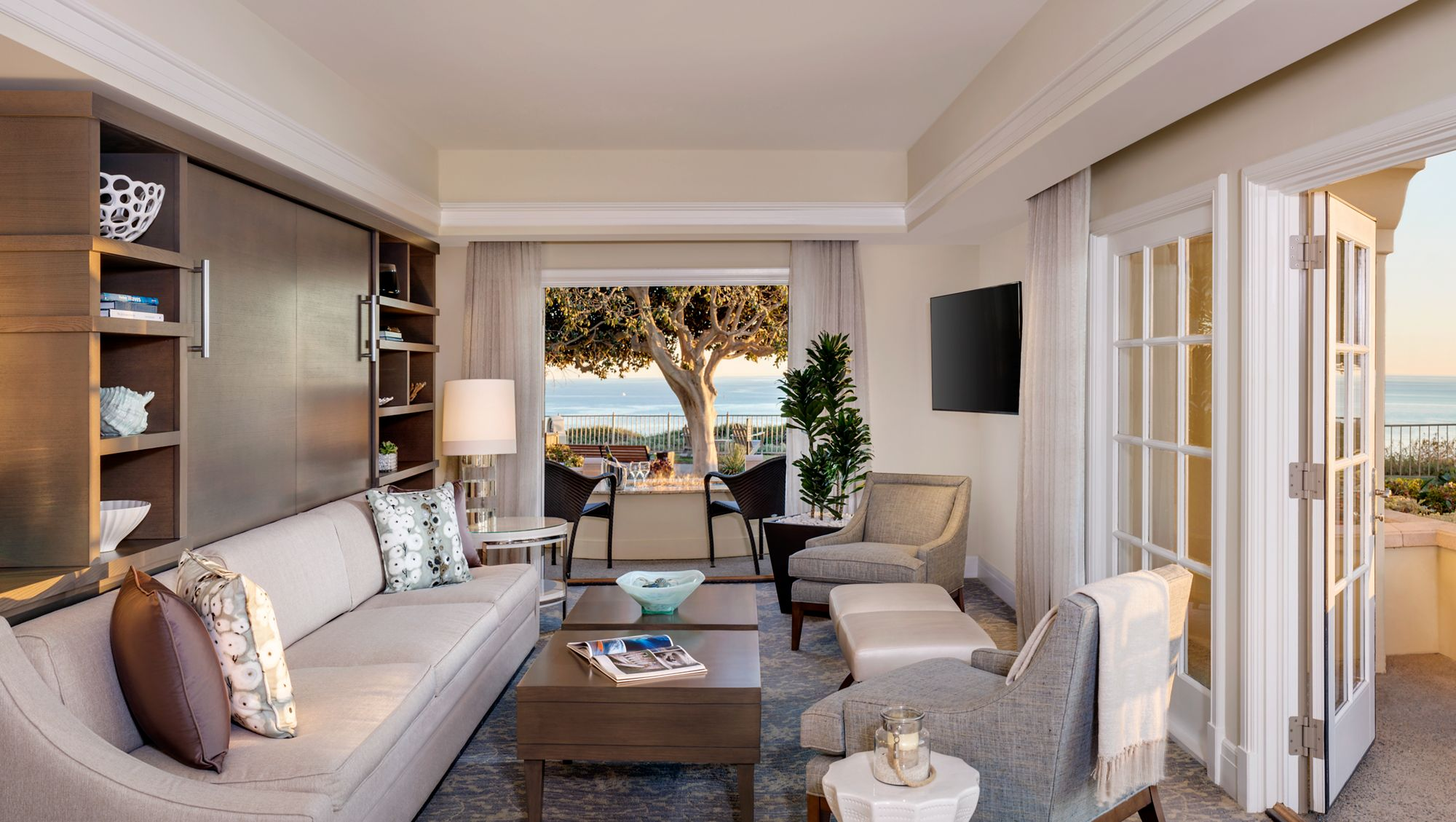A living room leads to outdoor, ocean-view spaces