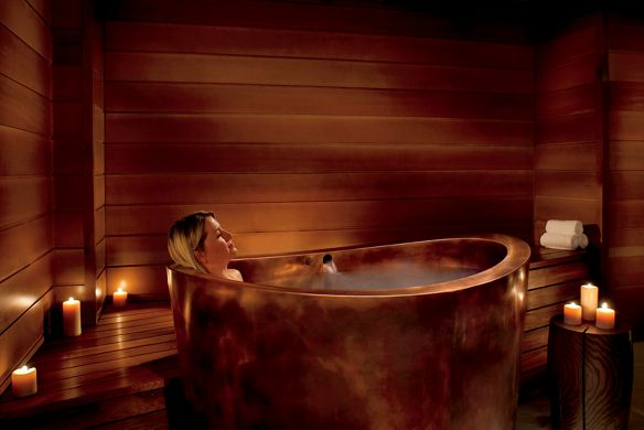 Woman soaks in a copper tub surrounded by candles