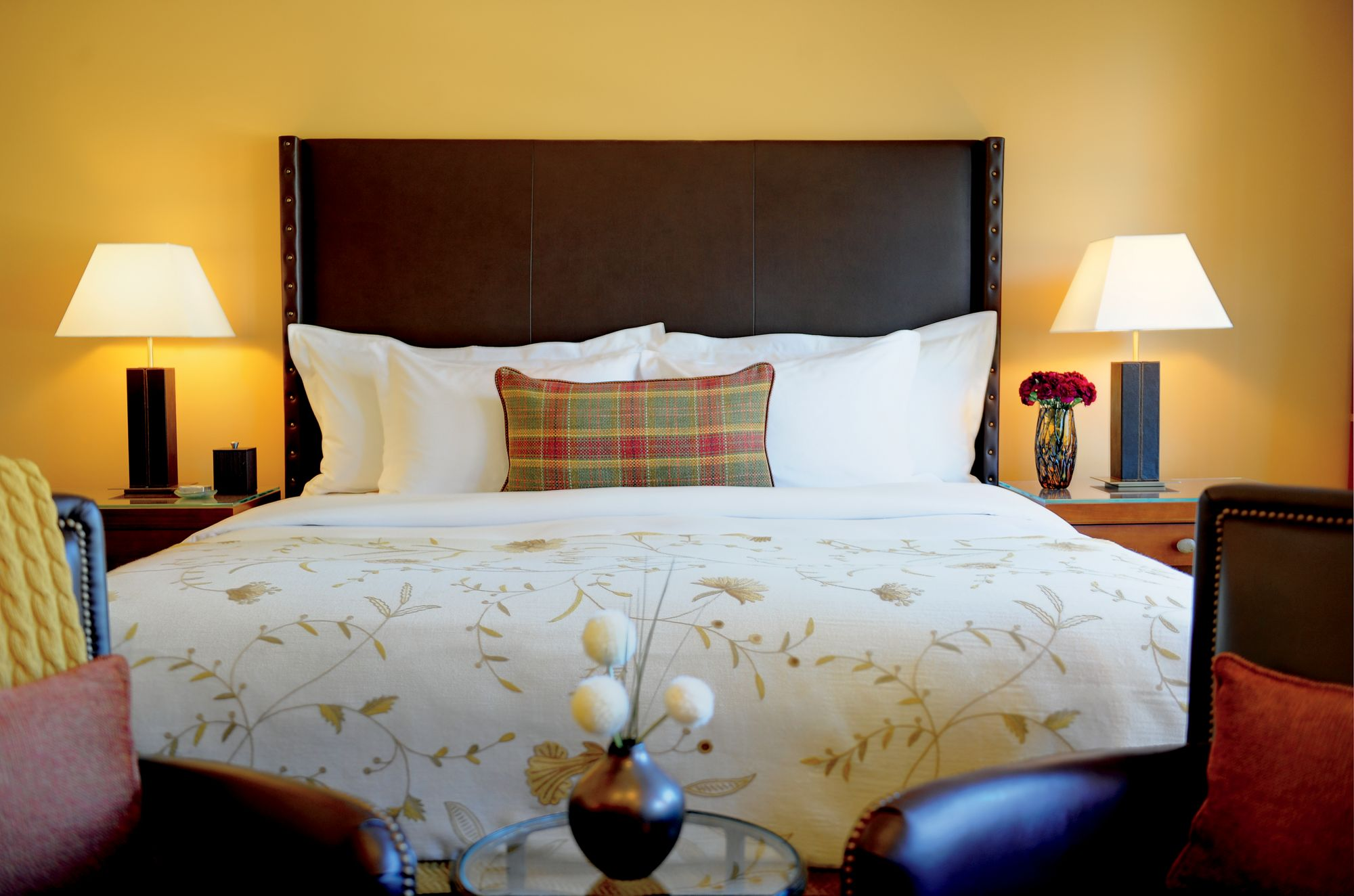 A double bed with two side tables and a small seating area at its foot