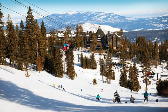 Skiers cruise down thesnow covered slope towards the hotel in the background, while others ride the ski lift