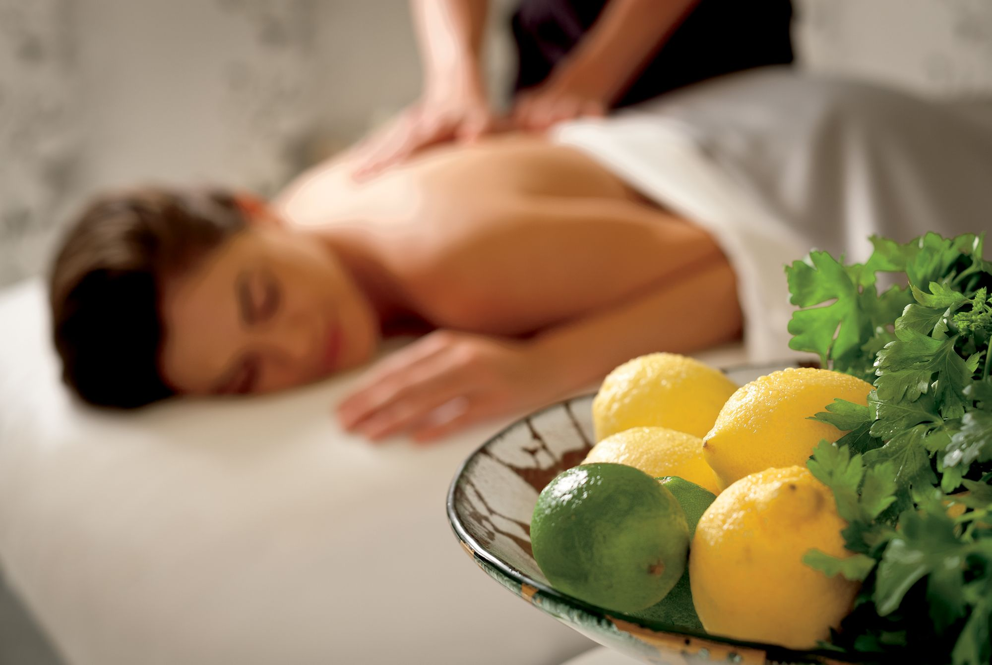 A woman lies on a massage table while a therapist works on her back with a bowl of lemons and limes in the foreground