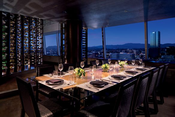 Long dining table with a glass wine case on one side and large windows overlooking the city at night