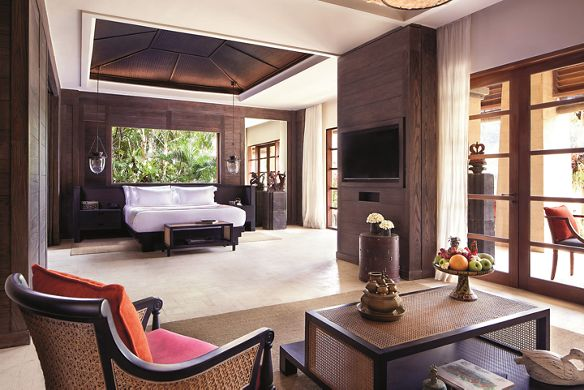 View to the king bed from the living room of the Reserve Suite, featuring wood accents, woven furniture and natural light