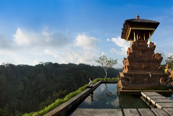 Woman meditates next to a still pool and temple-like structure overlooking the vast rainforest