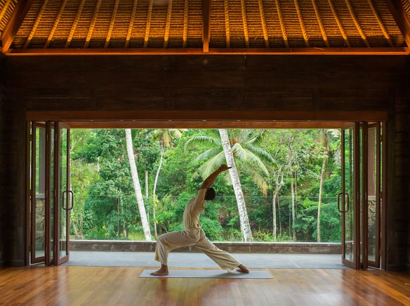 Person in flowy white linen performs yoga alone in a lofty room with retractable doors that open to the rainforest