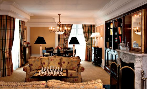 Living room with sofa, coffee table with chess set, dining table, mantle and bookshelves