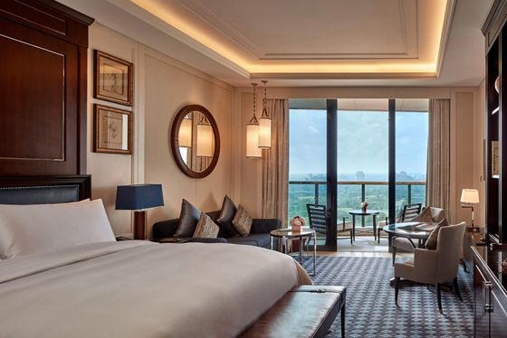 A room with a king bed, seating area and balcony