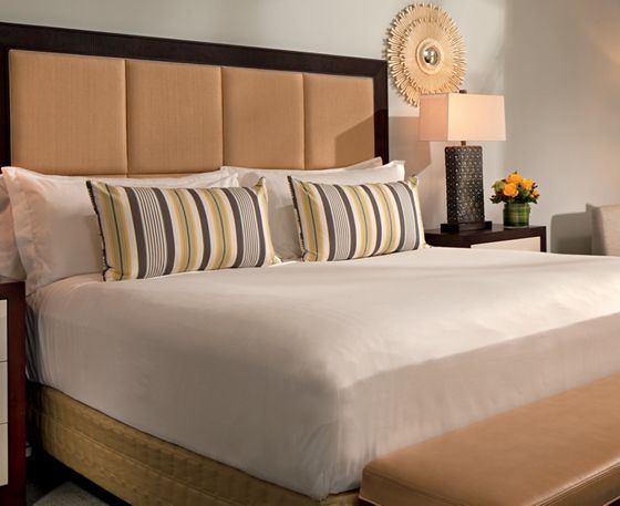 King-size bed with a bench at the its foot, a paneled headboard and  accents of espresso, blue and citron
