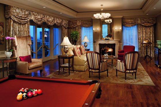 Pool table overlooking a seating area with a fireplace