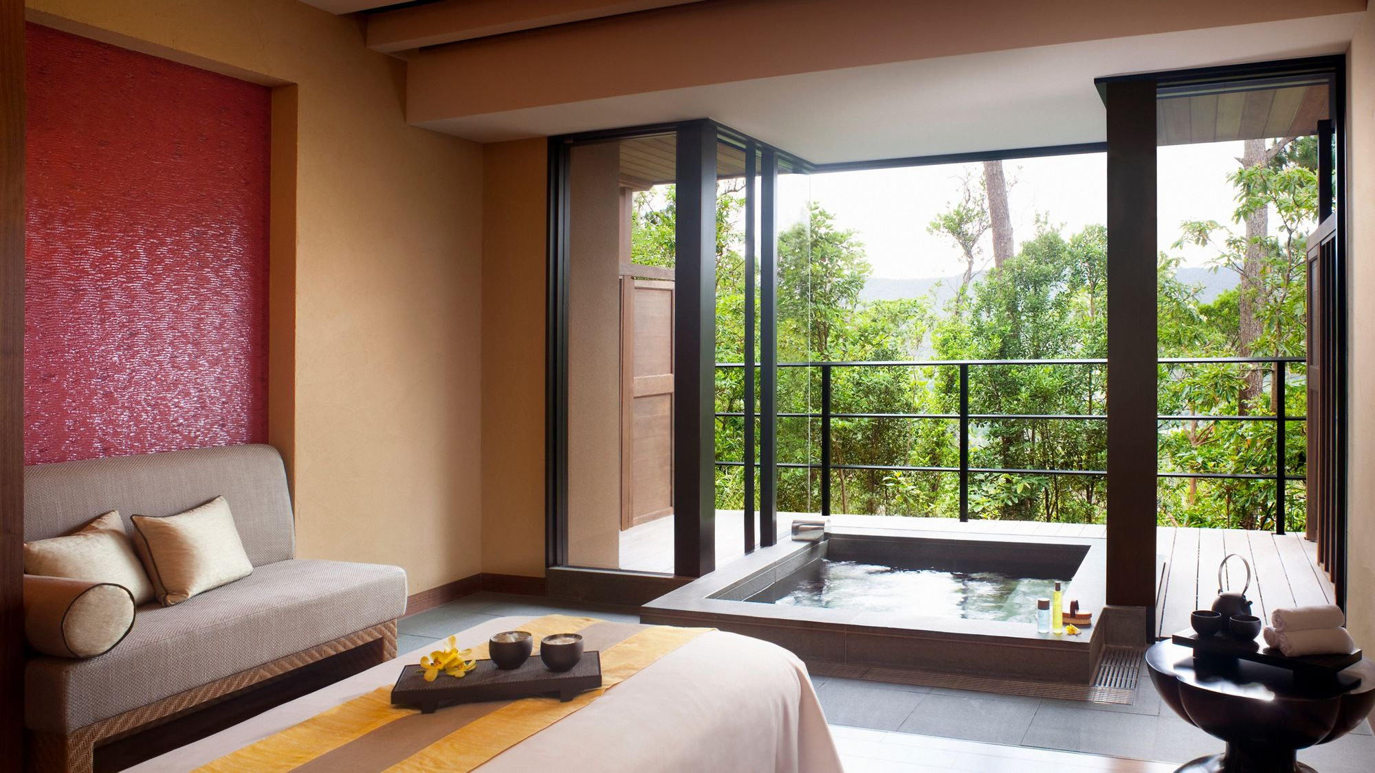 Spa treatment room with floor-to-ceiling windows and a private whirlpool
