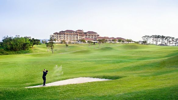 Golfer hitting out of a sand trap up the lush fairway toward the magnificent hotel building