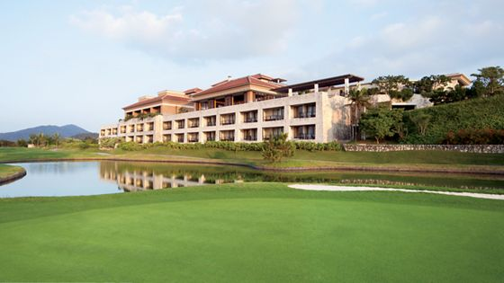 Exterior view of the resort and a small pond from the sloping, emerald turf of the golf course