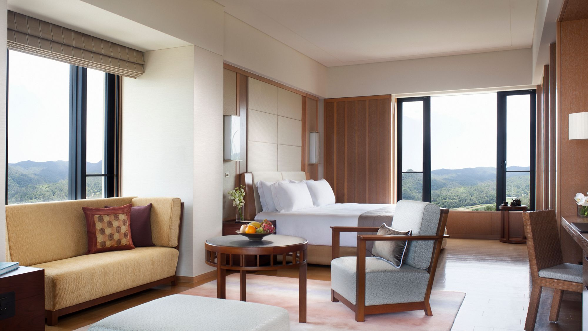Inside the Premier Deluxe Room with floor-to-ceiling sliding glass doors and views of the sea