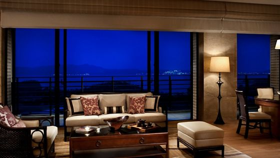 The spacious and well-appointed living room, windows and balcony in the Presidential Suite at the resort