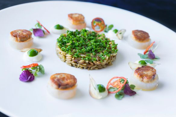 "A rice ""cake"" in the center of a plate with a few scallops and vegetable garnishes"