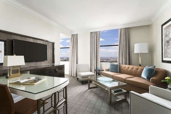 Executive Suite Living Room with sofa bed, desk, coffee table and entertainment area with flat screen TV.