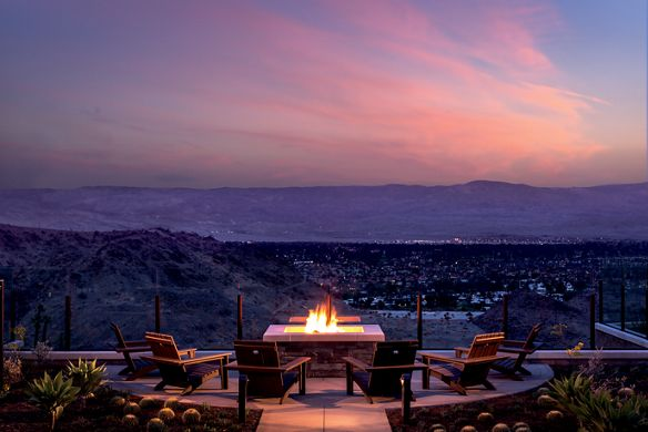 A seating area with a fireplace overlooking a valley at sunset
