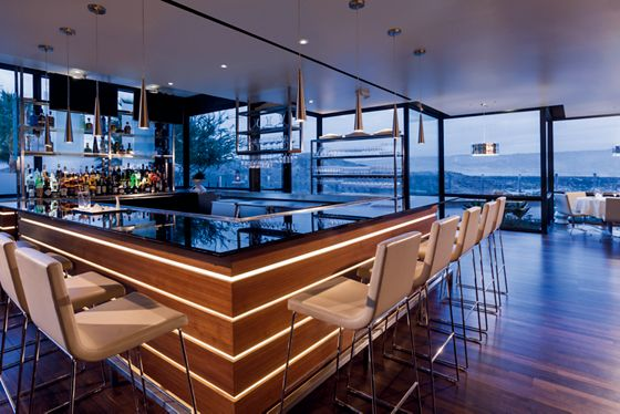 A square bar overlooks the mountains through floor-to-ceiling windows