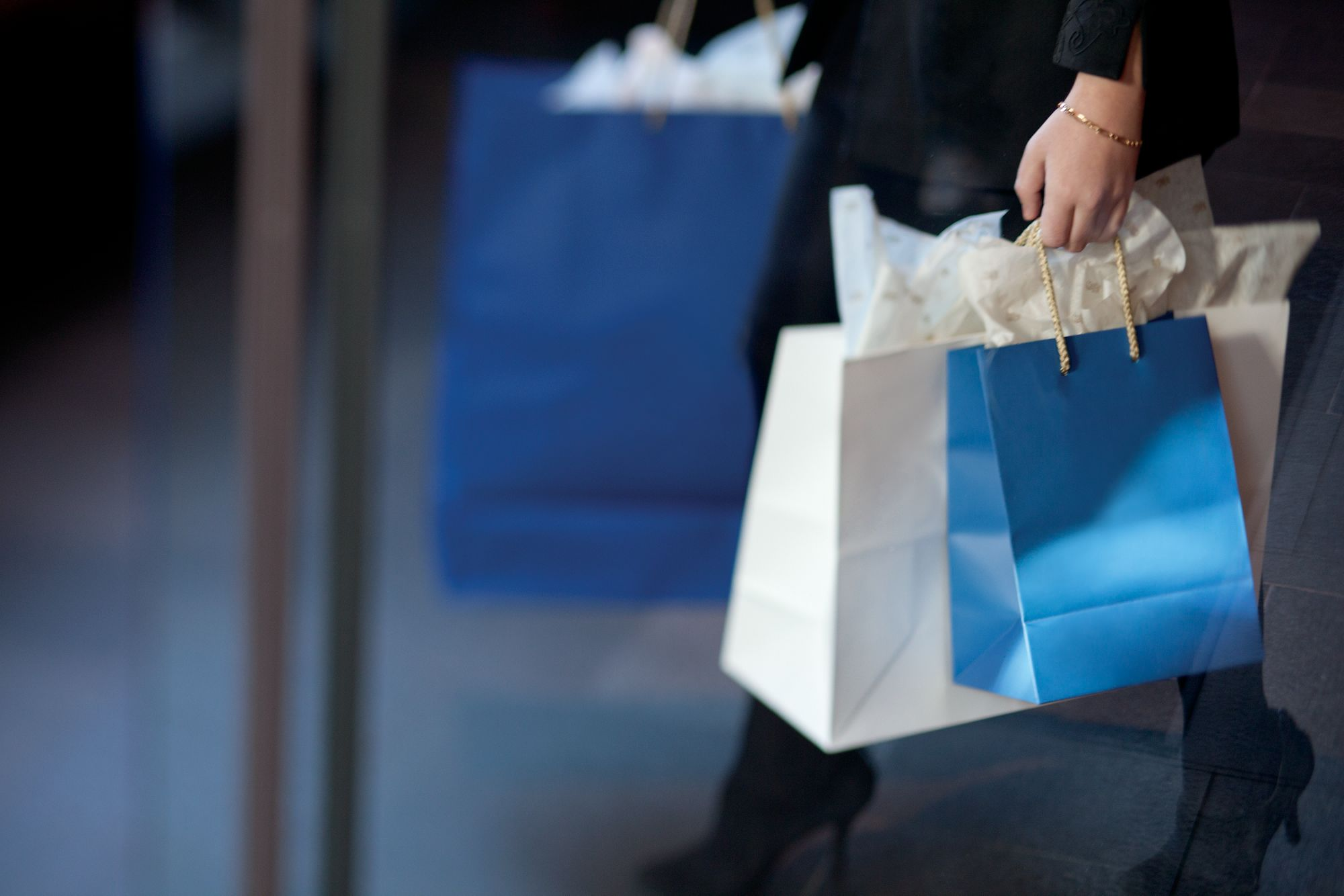 Lower half of a woman in a dark suit and heels carrying blue and white shopping bags