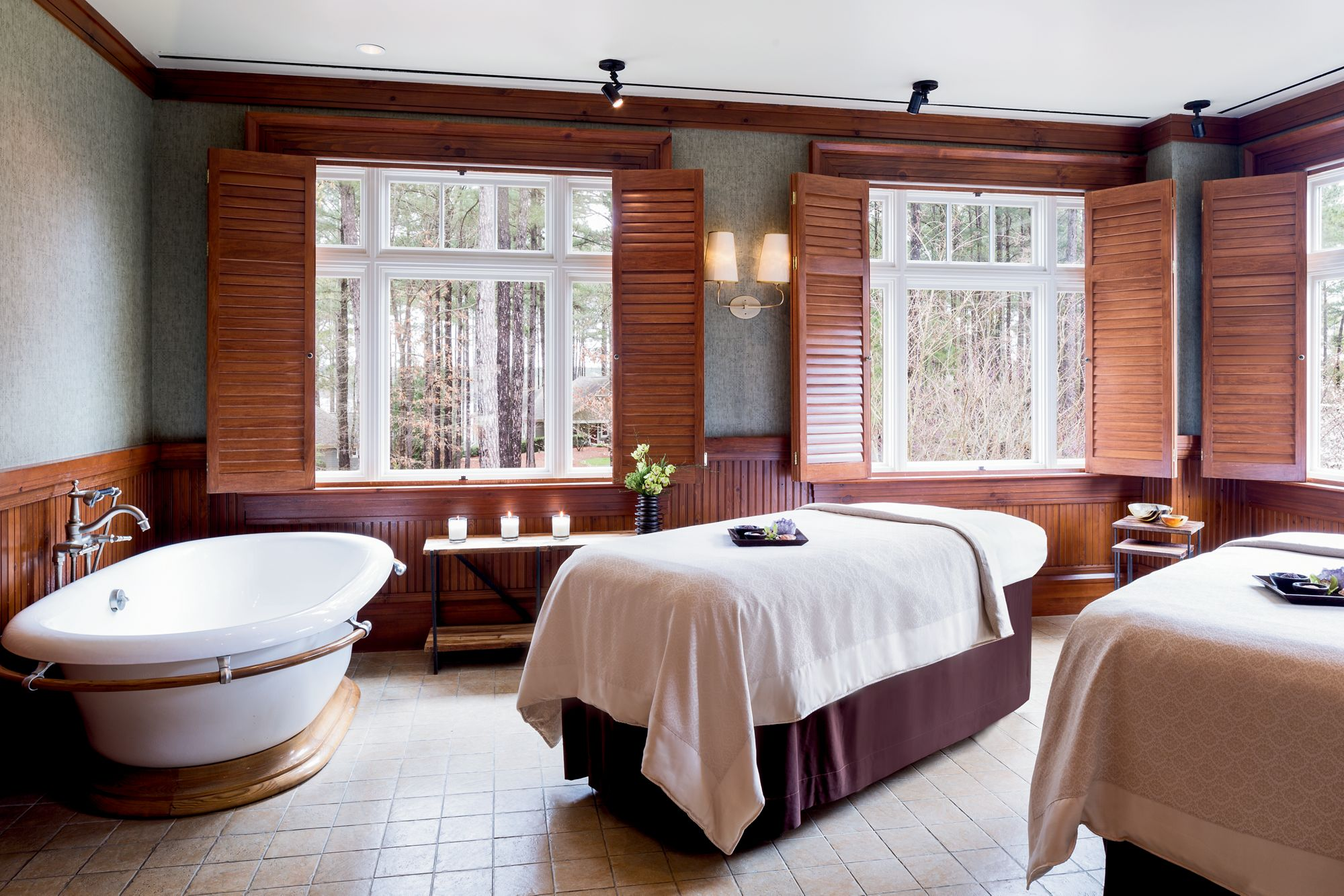 Two side-by-side massage tables in a room with a bathtub