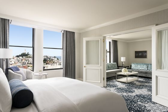 View of the bed and living room in the San Francisco Suite
