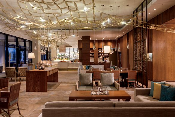 Lounge space with cozy seating areas, wood-paneled walls and net-like ceiling art
