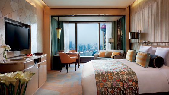 Guest room with a stone-like wall treatment and a sitting area with floor-to-ceiling views of the Pearl Tower