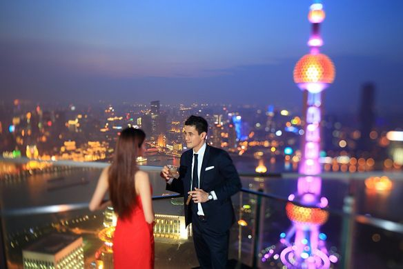 A woman in a red dress and a man in a jacket and tie sip drinks on a balcony overlooking the city at night