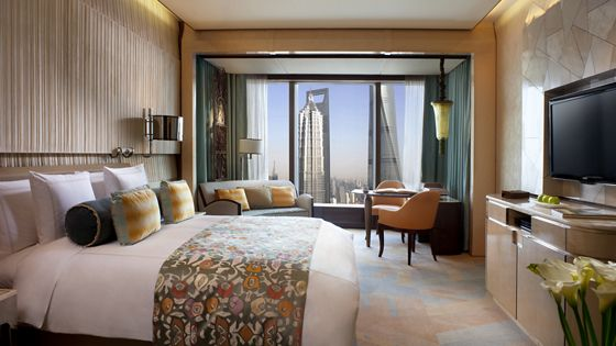Guest room with a king size bed, neutral color palette and a small sitting area that overlooks city views