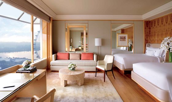 Large guest room with neutral colors, two beds, exotic wood paneling, mirrored surfaces and wall-to-wall windows