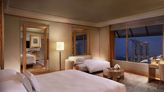 Guest room outfitted in honey-colored wood and carpet with wall-to-wall windows overlooking city lights in the evening