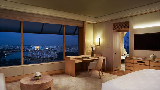 Guest room outfitted in honey-colored wood and carpet with wall-to-wall windows overlooking the city lights in the evening