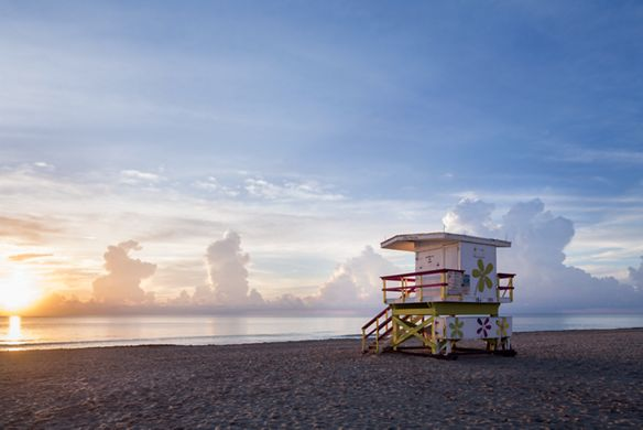 A lifeguard tower on the beach overlooks the ocean and a setting sun