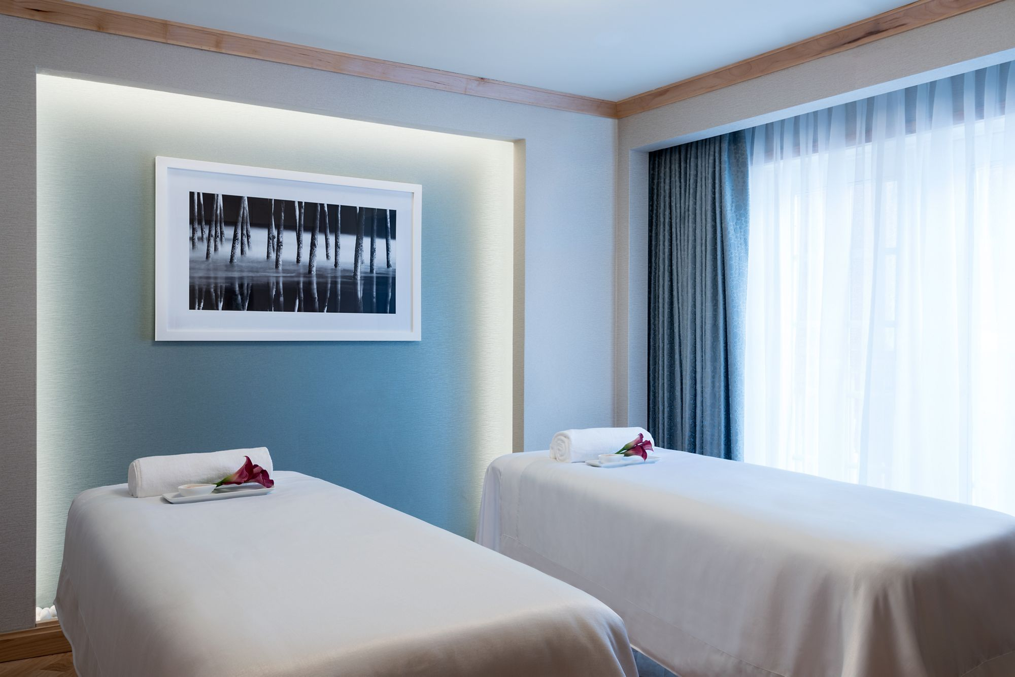 Two side-by-side massage tables in a room with a large window