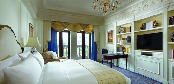 Room with a king bed, desk, armchair, glass doors leading to a balcony and a wall unit with flat-screen TV and books