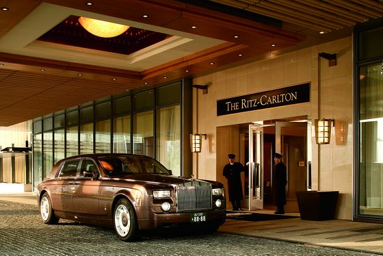 Rolls Royce parked in front of the hotel entrance with two doormen standing in attendance