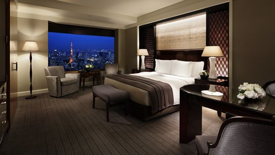 Guest room with dark grey carpet, dark wood accents, a king-size bed, a gleaming desk and skyline evening vistas