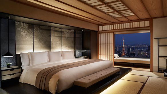 Suite bedroom with one large Japanese-style futon bed and a screen door open to evening skyline views