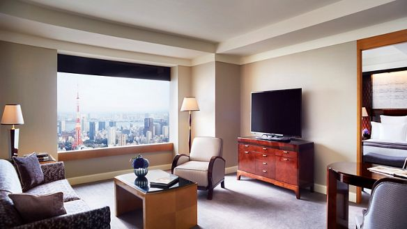 Living room and office in grays and whites with an expansive window overlooking the Tokyo skyline