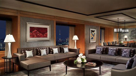 Suite living room with sleek gray couches, honey wood accents and evening views from expansive windows